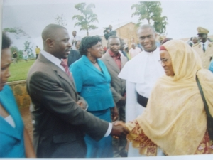 Headmistress shaking hands with the minister as manager of scholols looks on