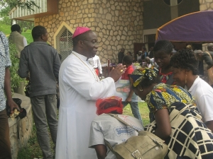 Mgr. Agapitus blessing some Christians