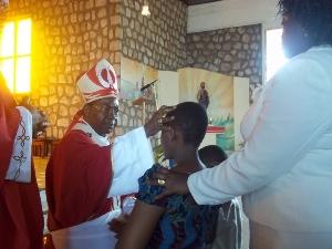 Archbishop Esua administering confirmation