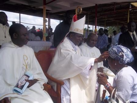 Bishop Nkea blesses the faithful as they present him gifts